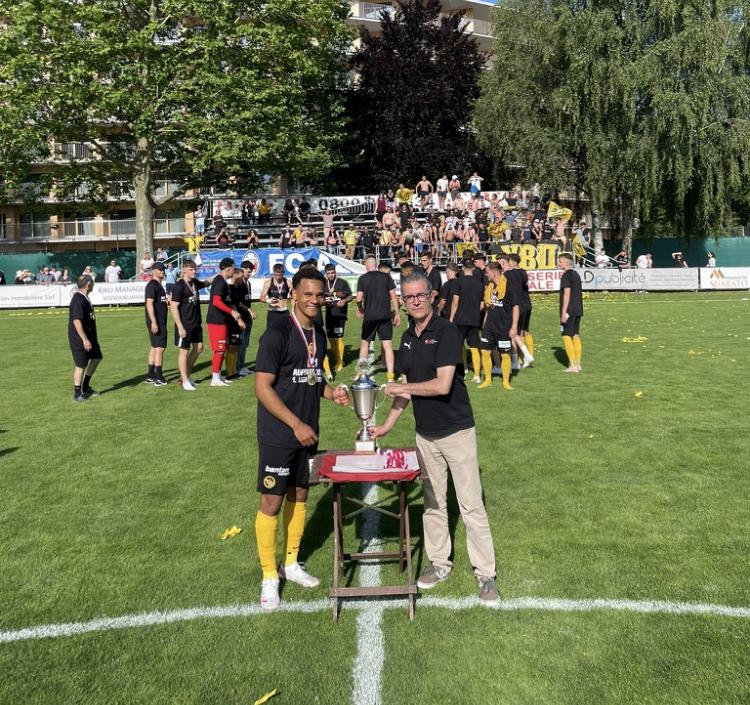 Marco Di Palma, Vizepräsident der Ersten Liga, übergibt YB-Captain Benjamin Kabeya den Pokal